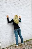 The girl costs near a white wall Royalty Free Stock Photo