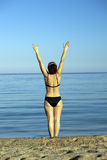 Girl costs at the sea, having lifted hands up. The harmonous girl ы a black bathing suit costs at the sea a view from a back, having lifted hands up Royalty Free Stock Image