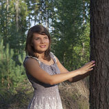 The  girl costs in wood. Near to a tree Stock Photo