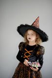 Girl in costume for Halloween. She in image the evil sorcerer. On the girl black-orange dress and a big hat. Girl holds a plate with candies and thoughtfully royalty free stock photo