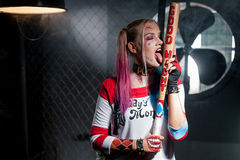 Girl in costume Harley. Cosplay. Girl in costume Harley. She stands with a bat and licks her bat. Close up. Cosplay Royalty Free Stock Photos