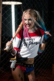 Girl in costume Harley. She stands with bat and gun. Close up. Cosplay Royalty Free Stock Image