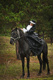Girl in costume on horseback Stock Images