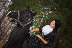 Girl in costume on horseback Stock Image