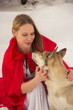 Girl in costume Little Red Riding Hood with dog like a wolf Royalty Free Stock Images