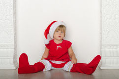 Girl in costume of Santa Claus sitting on floor Stock Photography