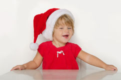 Girl in costume of Santa Claus at table and smiling Royalty Free Stock Photography