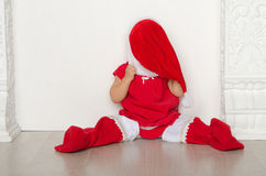 Girl in costume of Santa closes face sitting on floor Royalty Free Stock Photo