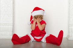 Girl in costume of Santa hides his face Royalty Free Stock Images
