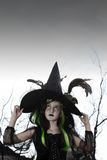 Girl costumed as witch looking up holding her hat Royalty Free Stock Images