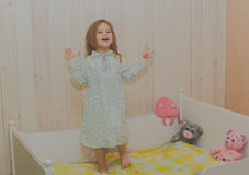 Girl in a cot does not want to sleep plays Royalty Free Stock Photography