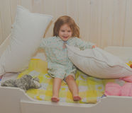 Girl in a cot does not want to sleep plays Stock Photos