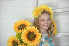 Girl in a cotton dress in a wreath of yellow flowers Stock Photography