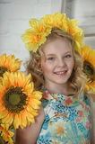 Girl in a cotton dress in a wreath of yellow flowers Stock Photos