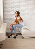 Girl on the couch. Girl in jeans sitting on the sofa Stock Photography