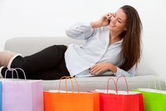 Girl on couch with mobile and shopping bags Stock Photos