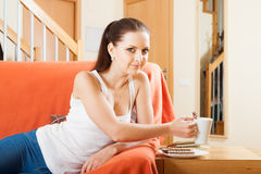 Girl on couch with mug of coffee . stock photography