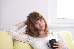Girl on the couch relaxing holding a cup looking at you. A young beautiful woman is drinking a cup of coffee or tea relaxing on the couch looking at you Stock Image