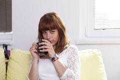 Girl on the couch relaxing and drinking. A young beautiful woman is drinking a cup of coffee or tea relaxing on the couch looking at you Royalty Free Stock Photos