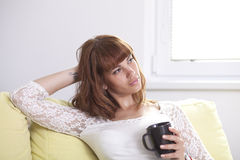 Girl on the couch relaxing. A young beautiful woman is drinking a cup of coffee or tea relaxing on the couch looking away Royalty Free Stock Image