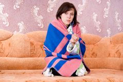 Girl on the couch with a thermometer Stock Photography