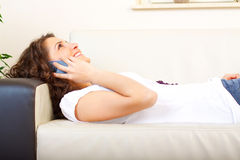 Girl on a couch using a mobile phone Stock Image