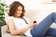 Girl on a couch using a mobile phone Royalty Free Stock Image