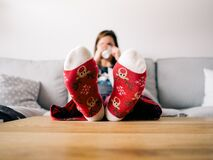 Girl on couch wearing decorated slippers Stock Images