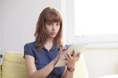 Girl on the couch working on the tablet. A young beautiful woman is working on her tablet sitting on the couch Stock Photo