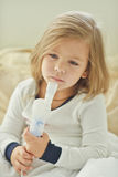 Girl with cough. Little girl with cough using inhaler at home Royalty Free Stock Image