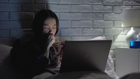 Girl coughing hard, suffering flu and insomnia, watching film on laptop at night. Stock footage stock footage