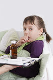 Girl coughing and lying in bed with medicine Royalty Free Stock Photography