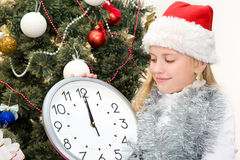 Girl counting the minutes in anticipation of Christmas. Girl in santa hat considers minutes before the start of Christmas holding in hands clock Stock Photo