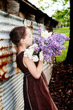 Girl in country dress smelling lilacs Royalty Free Stock Image