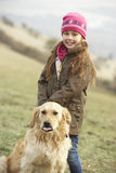 Girl on country walk with dog in winter Royalty Free Stock Images