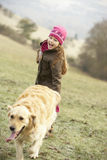 Girl on country walk with dog in winter Stock Images