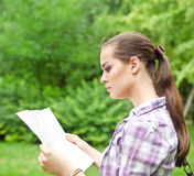 Girl in the countryside holding a map Stock Images
