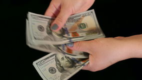 Girl counts money on a black background, slow mo.