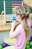 Girl counts on wooden abacus Stock Photo