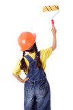 Girl in coveralls with paintroller. Girl in blue coveralls and hard hat with paintroller on the white wall, rear view, isolated on white Stock Photo