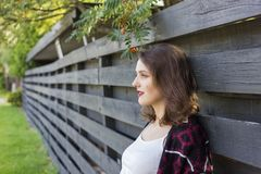 Girl covered with green tree branches in front of wooden fence. Wooden fence photoset. Girl covered with green tree branches in front of wooden fence Stock Photography