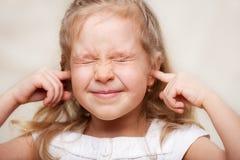 Girl covered her ears Stock Image