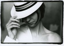 The girl covered her face with the brim of a hat. Attention! Image contains grit and other analog photography artifacts royalty free stock images