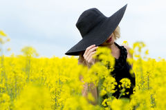 The girl covered her face with a hat in the field with flowers Stock Photos