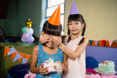 Girl covering birthday girls eyes and offering a gift Stock Photo