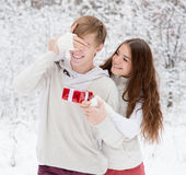 Girl covering boyfriends eyes with hands and giving a gift.  stock image