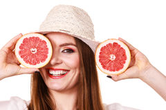 Girl covering eyes with two halfs of grapefruit citrus fruit Stock Images