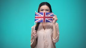 Girl covering face with British flag, learning language, education and travel. Stock footage stock video