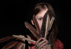 Girl covering the face with feathers Stock Photos