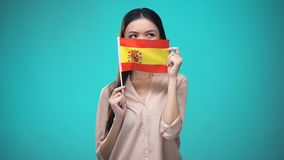 Girl covering face with Spanish flag, learning language, education and travel. Stock footage stock footage